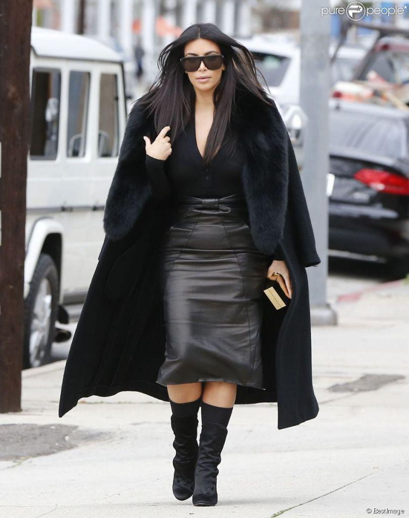 Kim Kardashian en jupe en cuir taille haute et manteau col fourrure total look noir